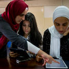 Muslim woman helps refugee student load information into an iPad Article 26 Backpack UC Davis