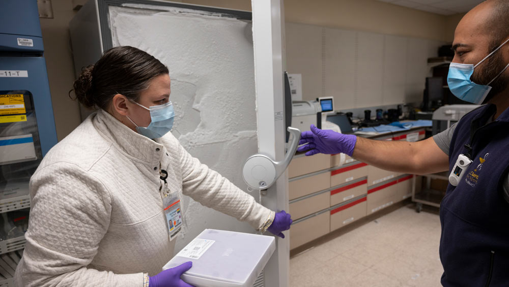 Woman in lab coat removes tray from freezer.