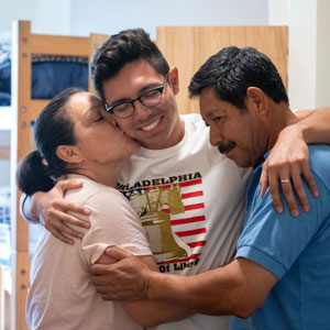 student hugging parents -