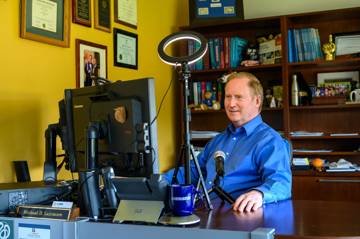 Michael Lairmore at desk with computer, microphone and lighting for podcast recording.