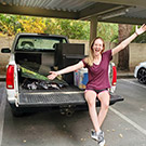 Woman sitting on bed of pickup truck