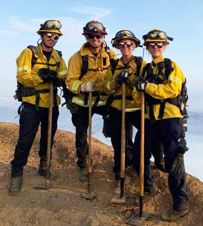 Campus fire crew poses at forest fire.