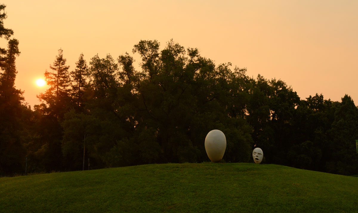 Two Egghead sculptures under hazy colored sky.
