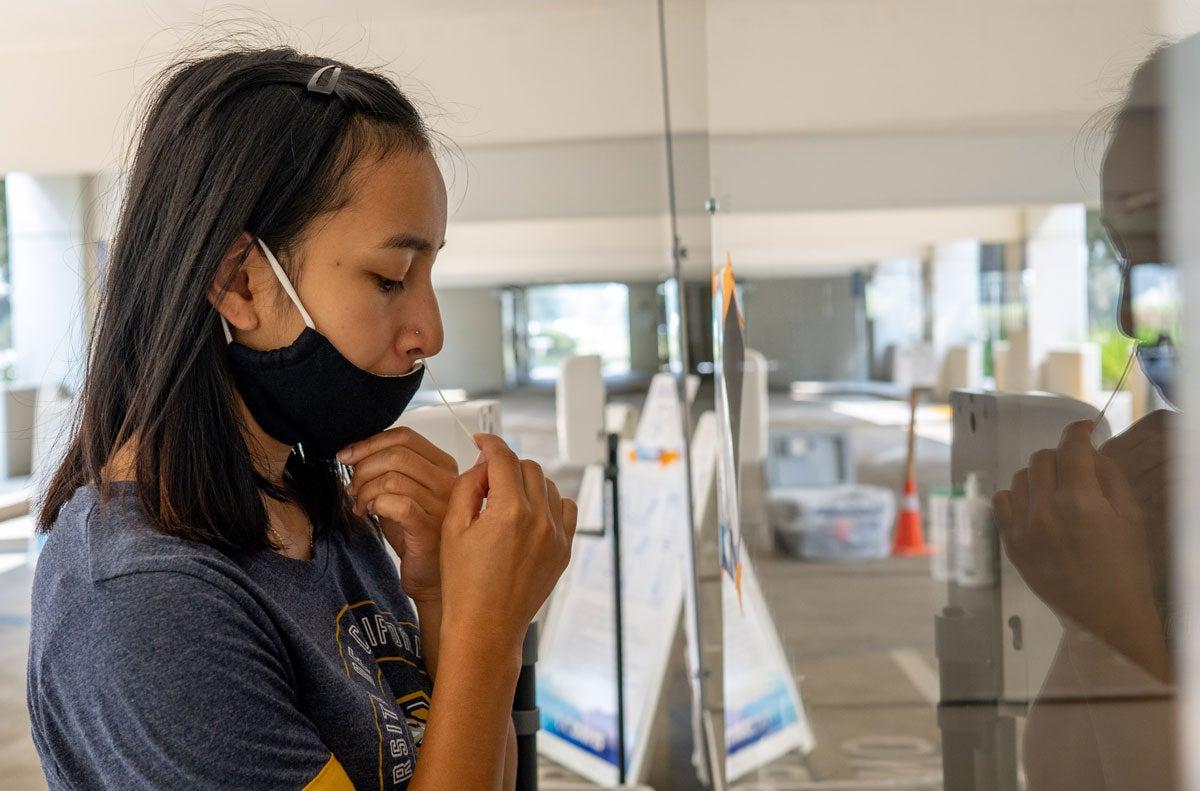 Katherine Yanogacio self-administers nasal swab test.