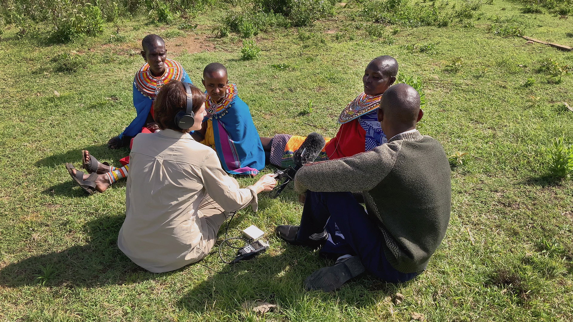 Women in Kenya talk with American woman reporter with microphone