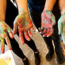 art students showing hands covered in paint