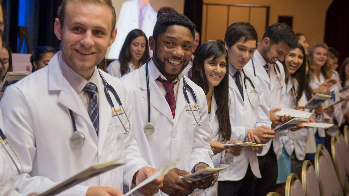 A line of medical students from UC Davis in white coats being inducted into the class