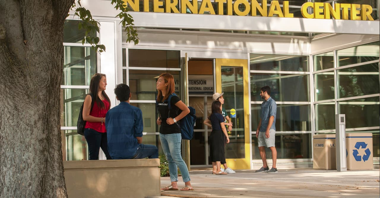 A small group of students talking outside the International Center  -  International Admission