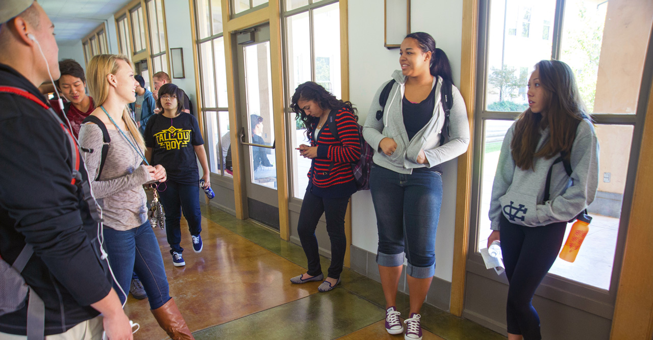 students gathering for a class and chatting in a hallway - transfer application timeline