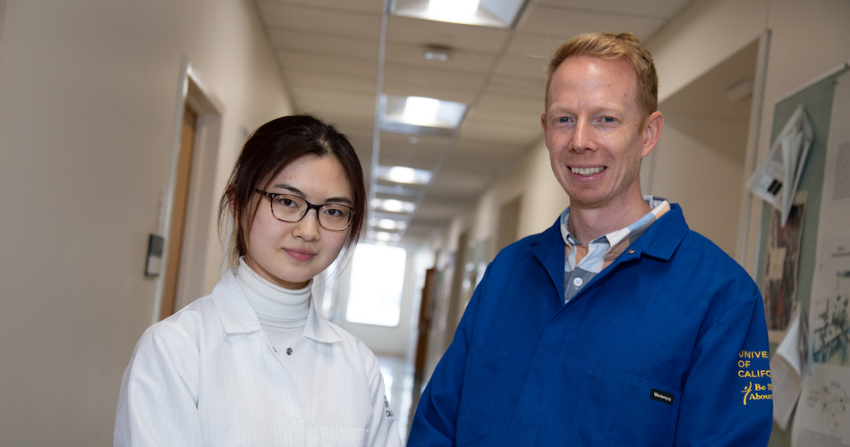 Li stands in a hallway wearing a lab coat next to her advisor.