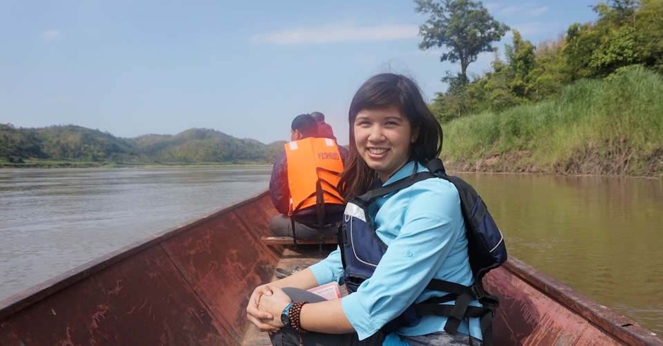 Erin is pictured smiling on a boat in a river.