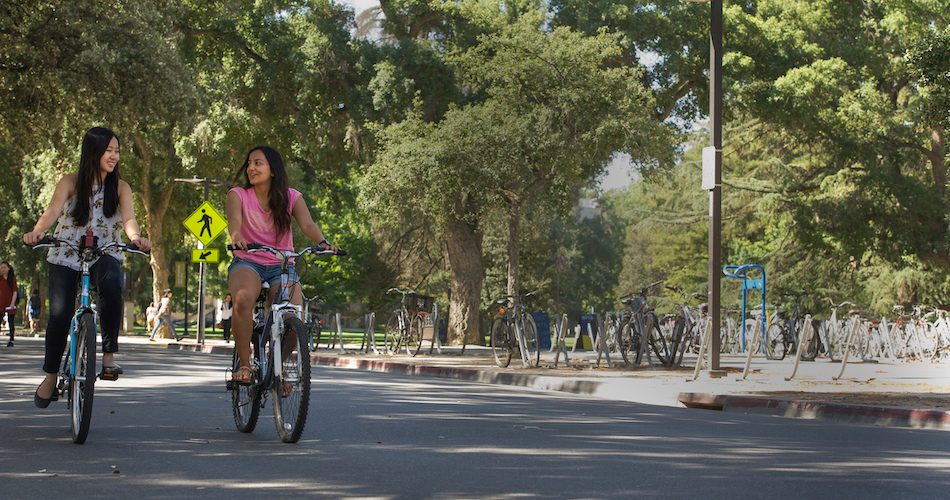 3.Managerial Economics majors Kristi Juwono (floral shirt) and Anshita Jain (pink shirt) are photographed with their bikes near the Social Sciences building on July 1, 2016. ALthough both women are from Jakarta, Indonesia, they didn't become friends until meeting at UC Davis. They are both peer advisors.  Karin Higgins/UC Davis