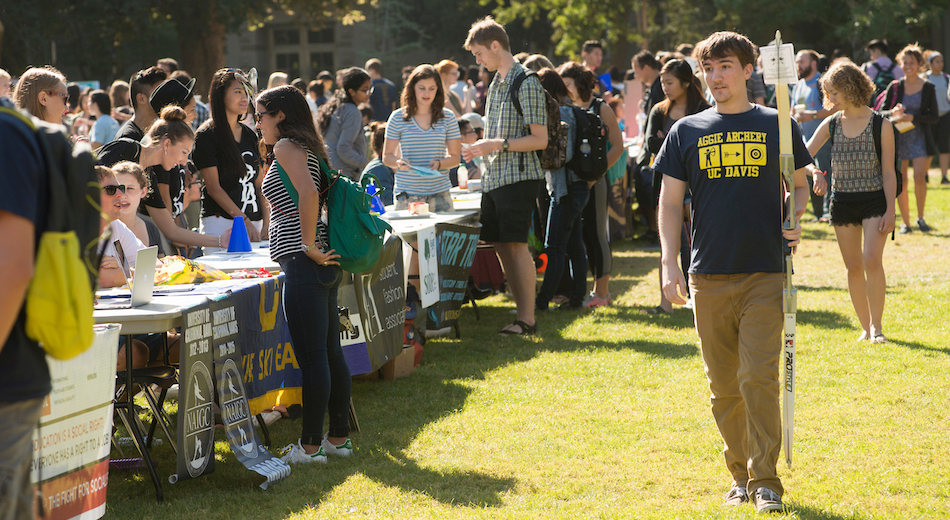 Students are outside in a field tabling to advertise their clubs.