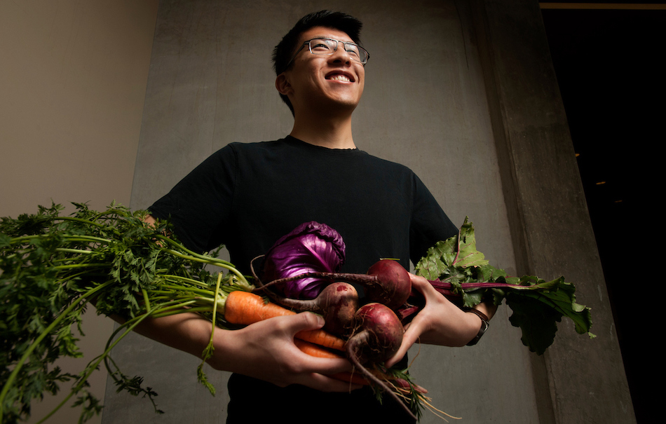 Student smiles while holding a bundle of bright vegetables.