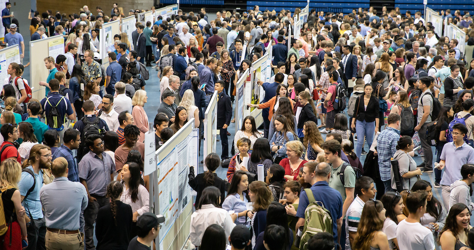 A large amount of students visit booths in a crowded pavilion.