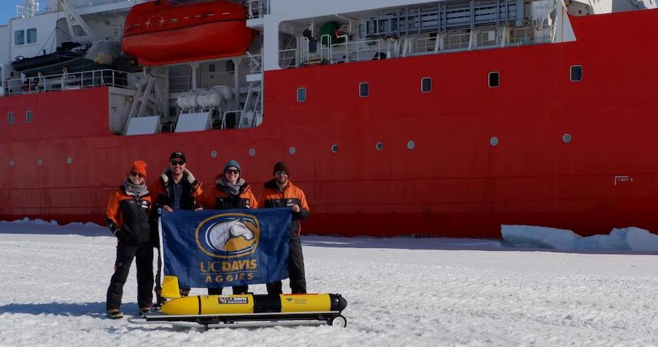UC Davis doctoral students Cordielyn Goodrich, Andrew Friedrichs and Jasmin McInerney with EPFL's Sebastian Lavanchy and the glider Storm Petrel on the ice beside icebreaker R/V Araon at Jang Bogo Station in Antarcticain January 2019. (Joe Haxel, OSU/NOAA)
