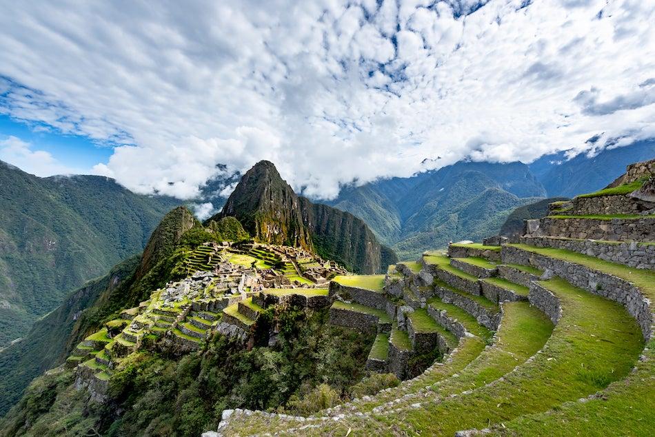An overhead view of misty Machu Picchu green mountains