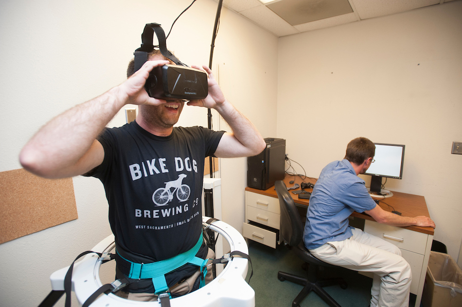 A man smiles in VR goggles in a lab.