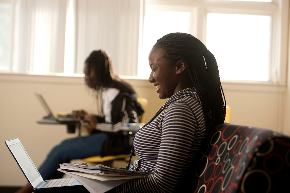 Two students study and smile in front of their laptops.