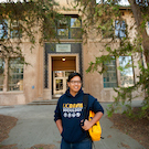 A student in a sociology sweatshirt stands outside of a campus building.