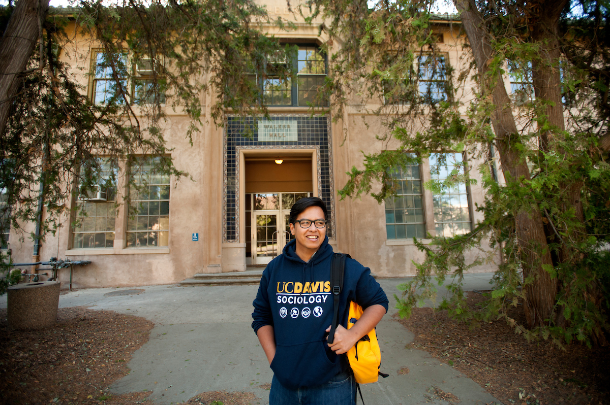 A sociology grad student wearing glasses and a sociology sweatshirt stands in front of a campus building with a backpack.