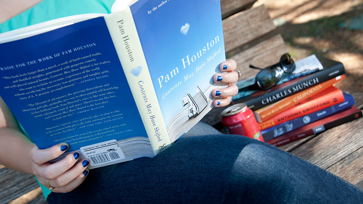 Woman reading Pam Houston book on a bench next to a pile of books