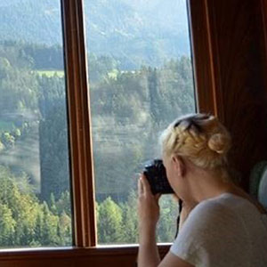 Woman with back to us shooting a photo out of a train window at mountains