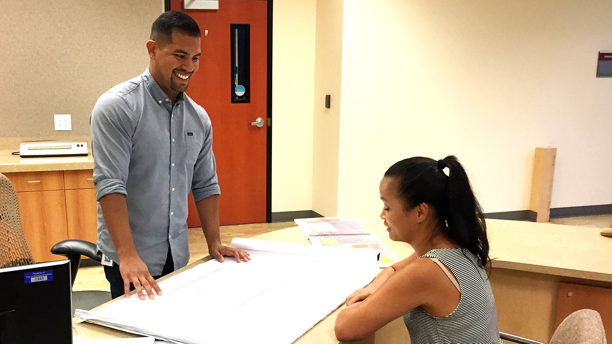 Community and regional development major Nick Sosa speaks with a colleague in the city of Rancho Cordova