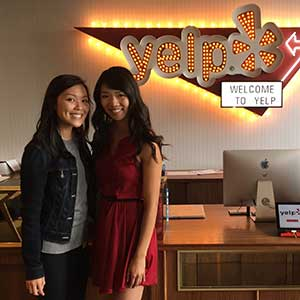 Two women posing in front of a Yelp sign