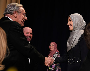 Washington Post journalist Bob Woodward shaking UC Davis alumna Sawsan Morrar's hand