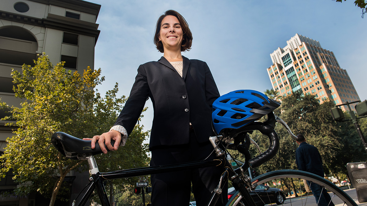 Alumna Sydney Vergis posing with a bike and helmet in downtown Sacramento