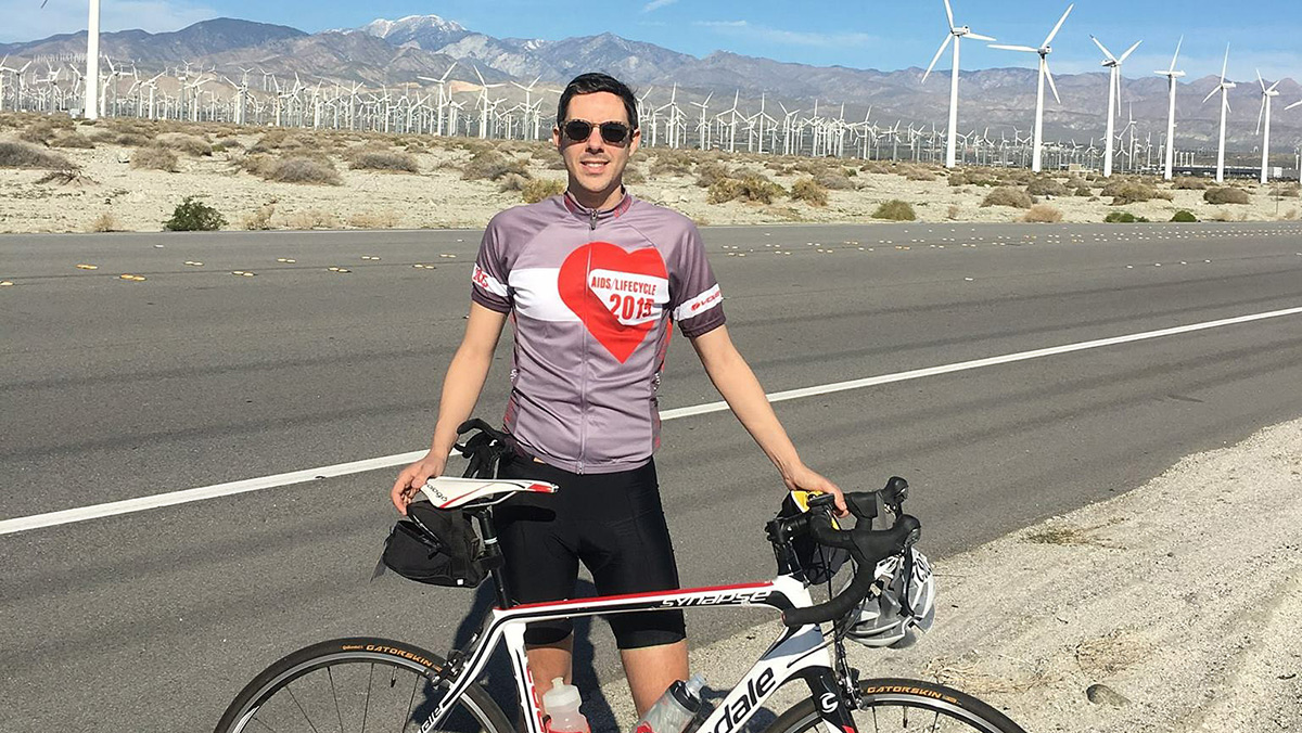 International relations graduate Tim Mizrahi poses with road bike next to highway with windmills in the background