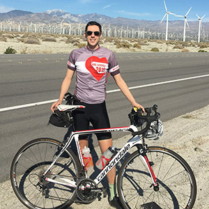 Tim Mizrahi posing with a road bike next to a highway with windmills in the background