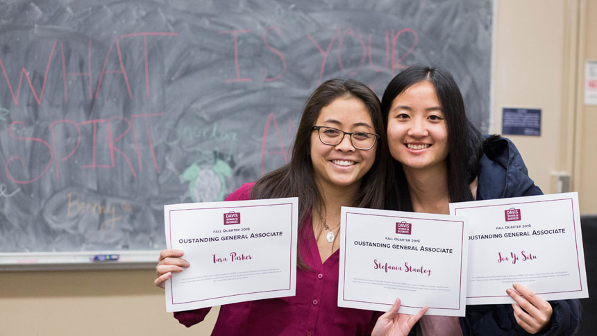 Two female students pose with award certificates