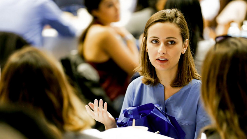 Woman in scrubs talking in a conference
