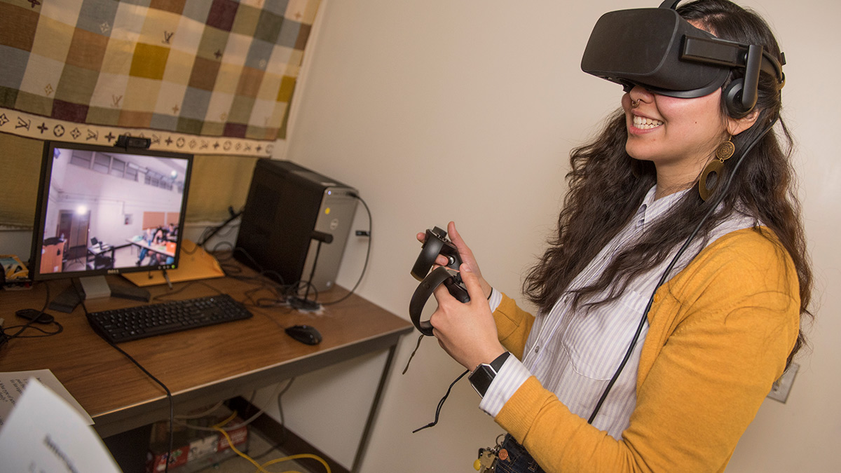 Communications graduate student Gracie Wolff wears a virtual reality headset to study the effects of role playing on public persona
