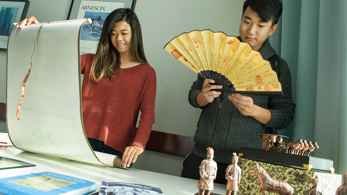 Senior communication major Karice Hui, left, and senior economics major Yongcong Cen view Asian art and cultural items
