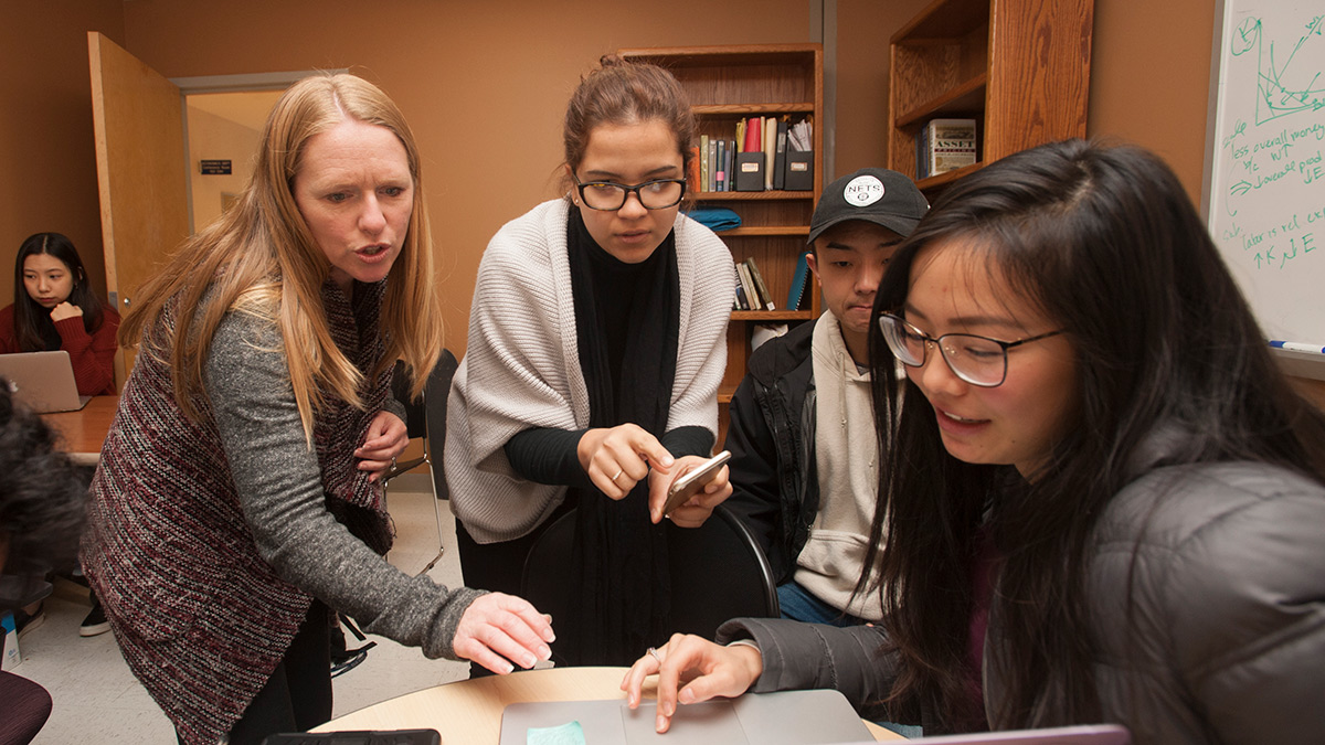 economics lecturer Janine Wilson discusses a theory with Andrea Romero, Daniel Moon and Julia Tien, all economics majors