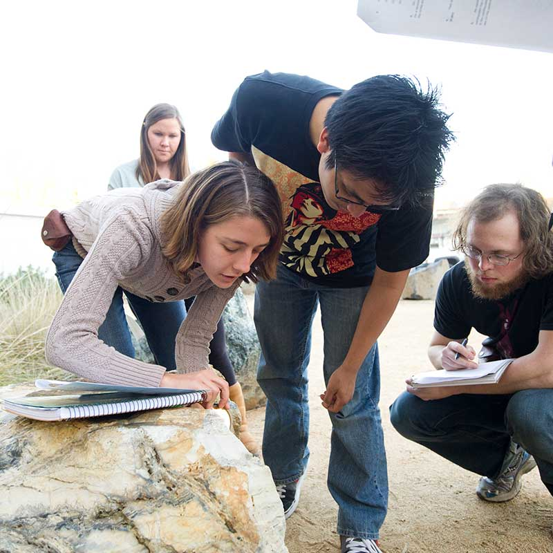 Female and male students study a rock