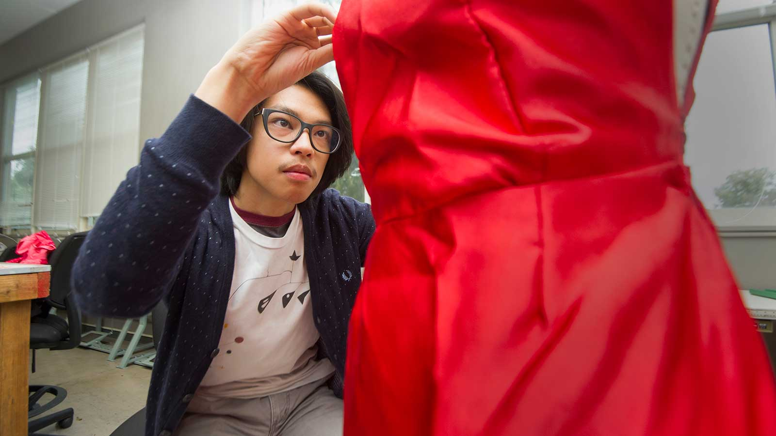 Male student adjusting a red dress on a manikin