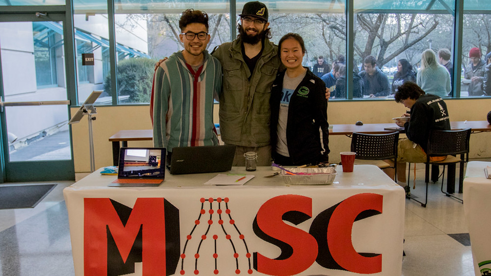 Two male and a female student standing behind a table with MASC, Material Advanatage Student Chapter