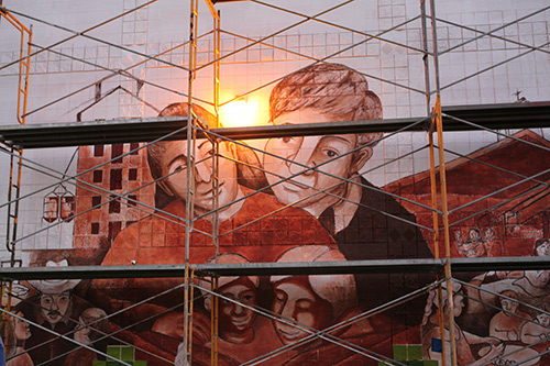 A mural of a man and woman with scaffolding in front