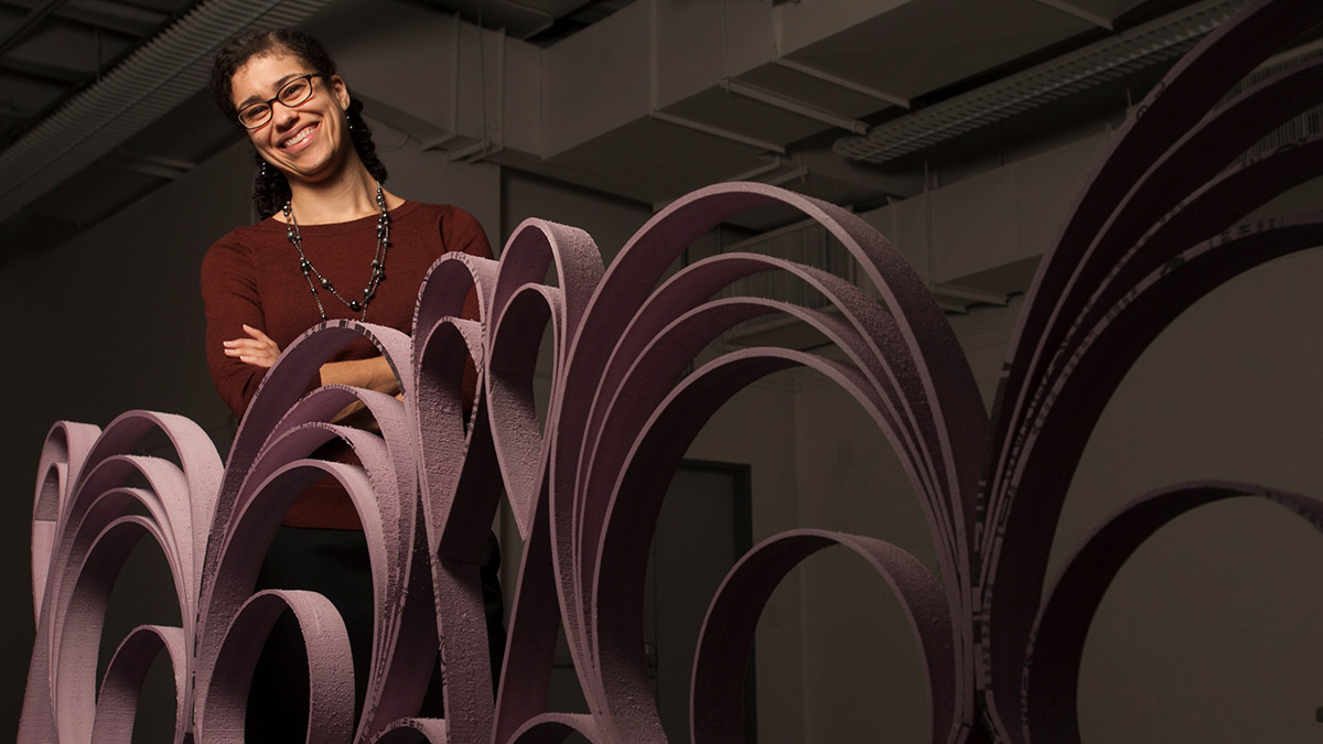 Ariel Collatz, undergraduate programs supervisor and undergraduate advisor, standing behind a sculpture