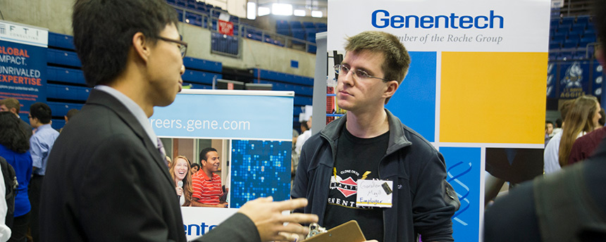 Gordon Magill, right, a Genentech employee and UC Davis alumni, listening to a student at a career fair