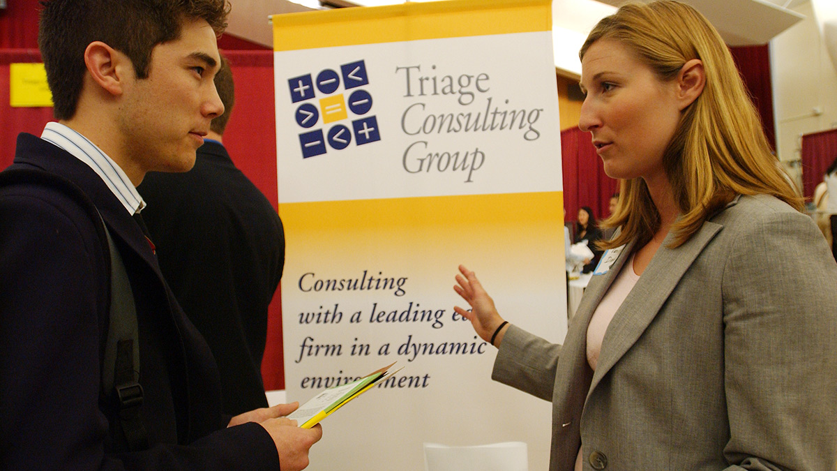 Male student listening attentatively to a female company representative at a career fair