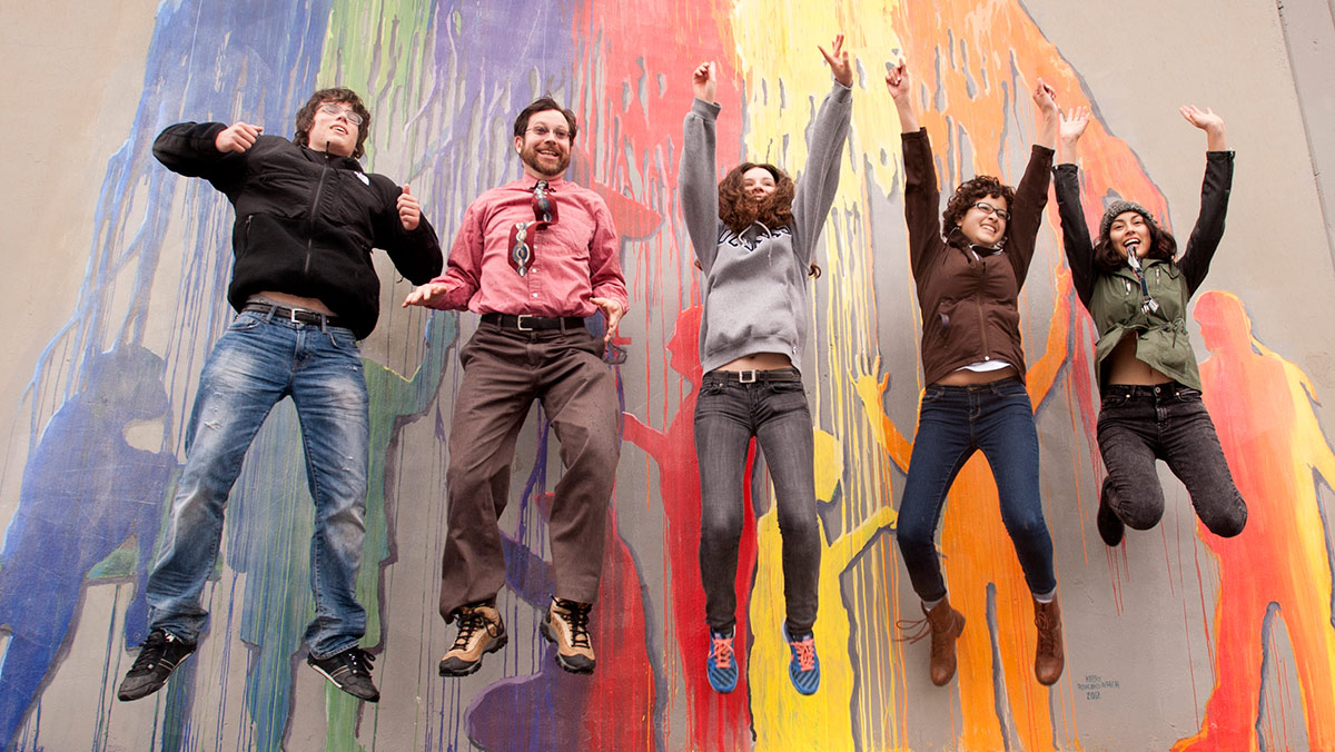 Several people jumping in the air with a colorful mural behind them