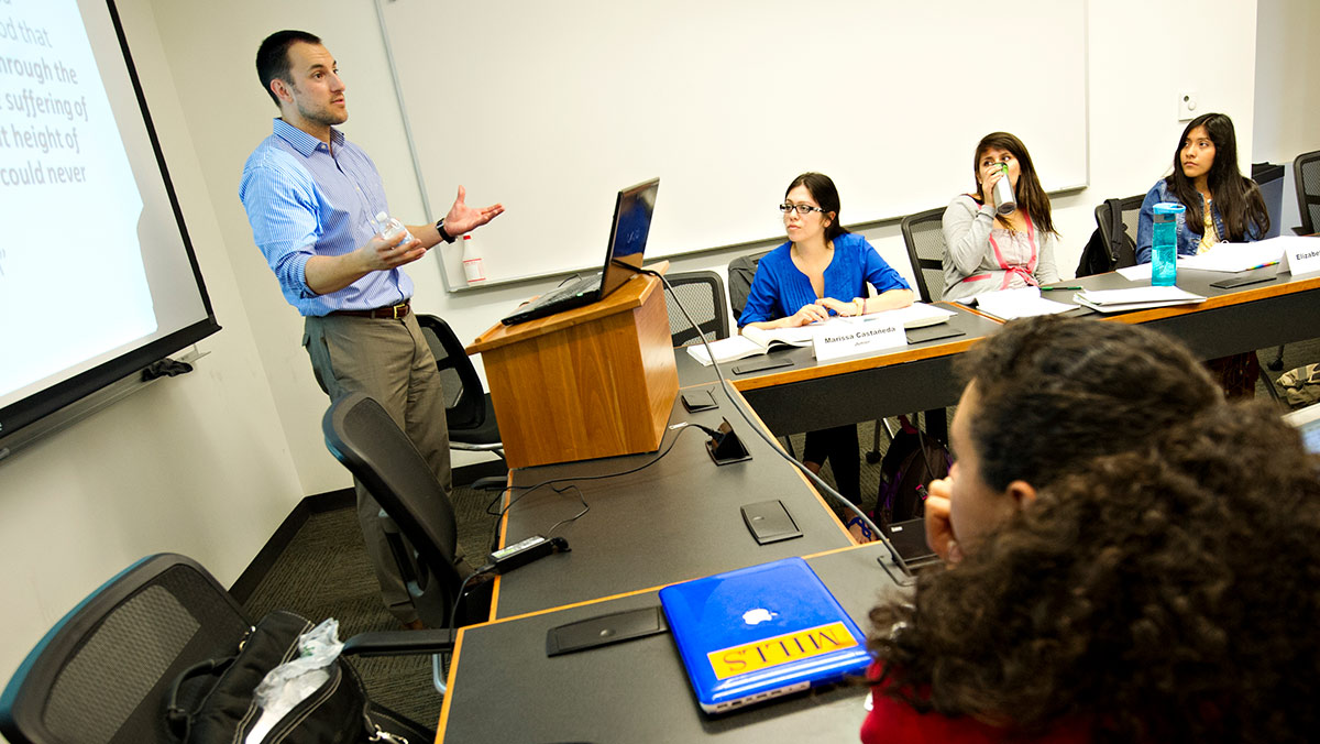 Man lecturing in a classroom with women sitting at long tables