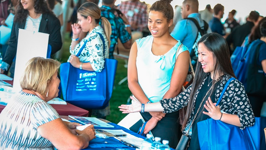 students visiting a conference booth
