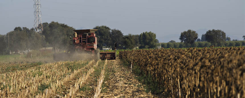 a tractor in a field stirs up a dust cloud that lowers air quality