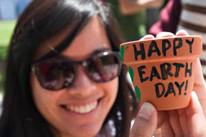 "A woman holds up a painting that reads ""Happy Earth Day"""